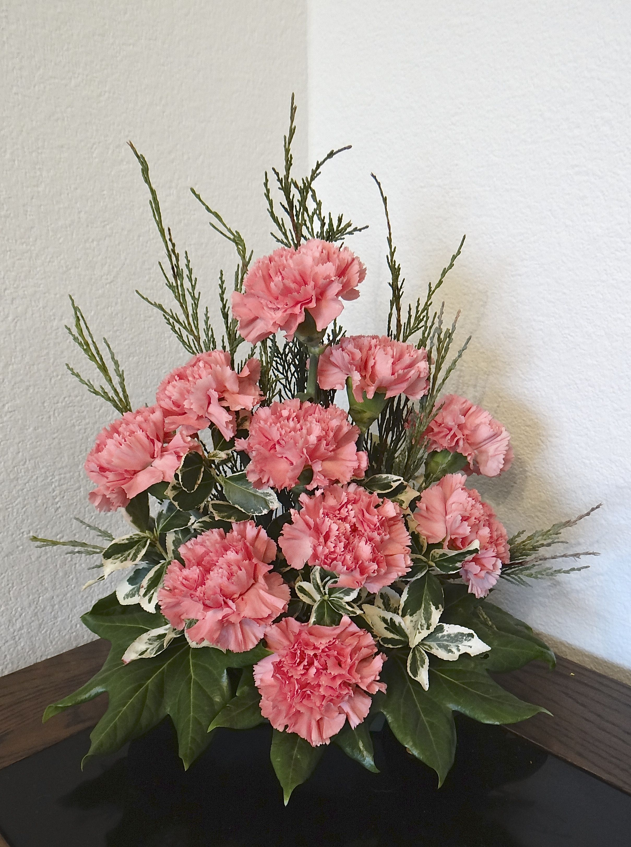 Pink Carnations With Some Fir Branches And Fatsia Leaves This