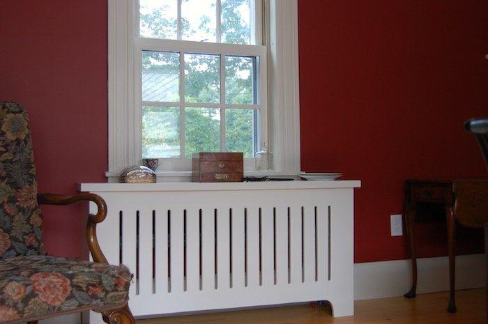 weiße Heizungsverkleidung im Kontrast mit den roten Wänden, bunter