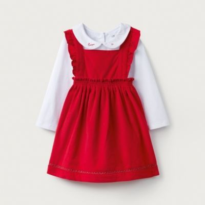 Simple but beautiful, our pinafore-style red cord dress features lovely little frills on the straps, a cross back and a sparkling silver trim along the hem. It is the perfect shape for layering over our accompanying Peter-Pan-collared bodysuit, which has little love and heart embroidery on the collar. A gorgeous outfit for Christmas and beyond.Design & Fit •	Pinafore dress and bodysuit set•	Frill straps and silver trim on the dress•	Love and heart embroidery on bodysuit•	Perfect for partiesFabri
