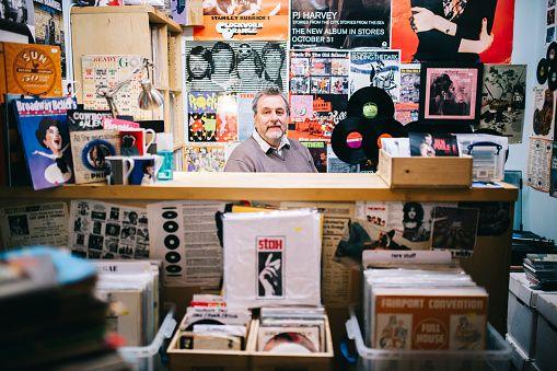 Portrait, man behind checkout counter, vinyl record shop, pop music