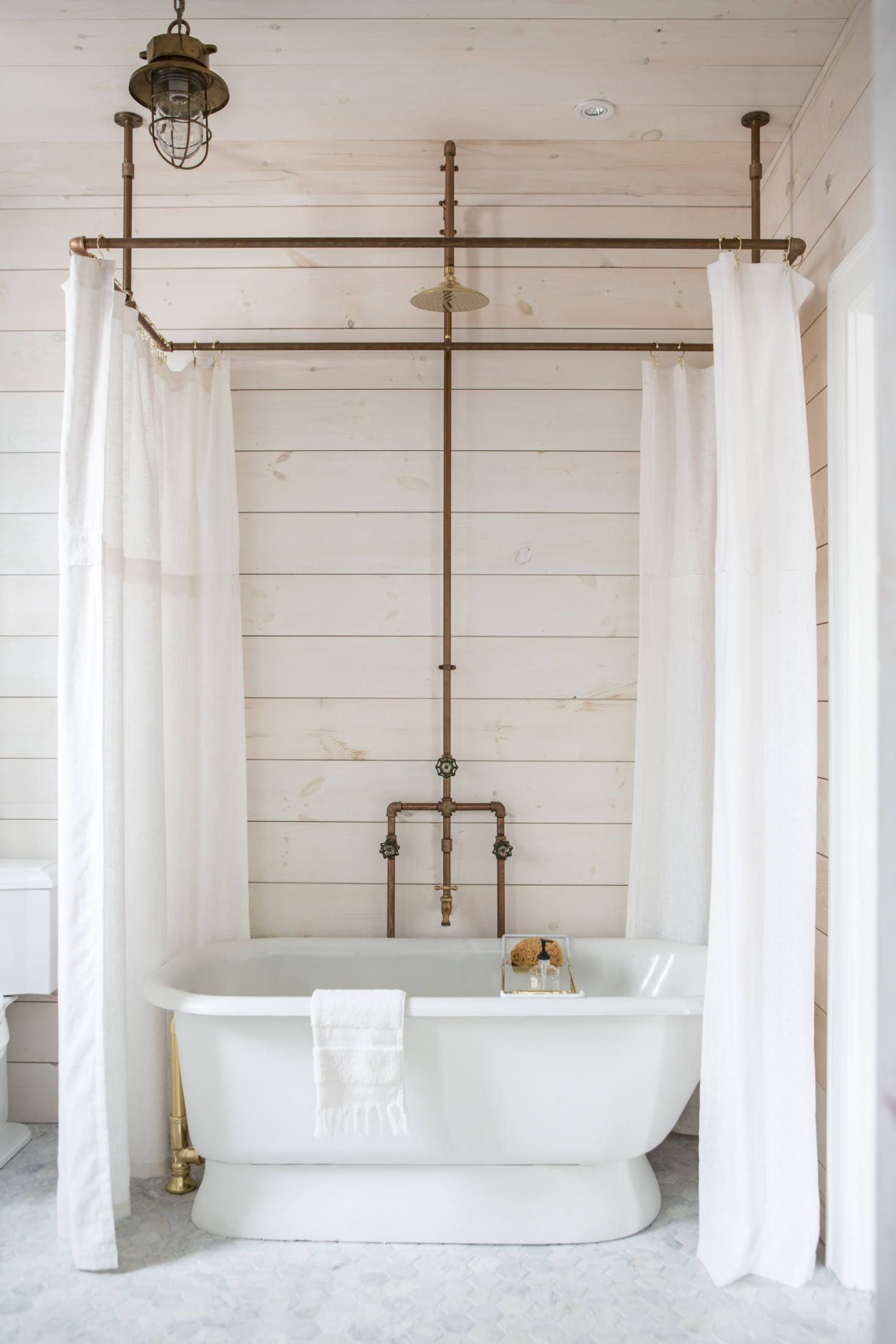 An Antique Soaking Tub Is Ringed By Custom Linen Shower Curtains