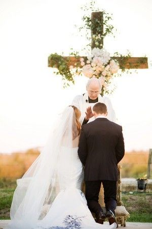 Large wooden cross with flowers and vines at wedding.