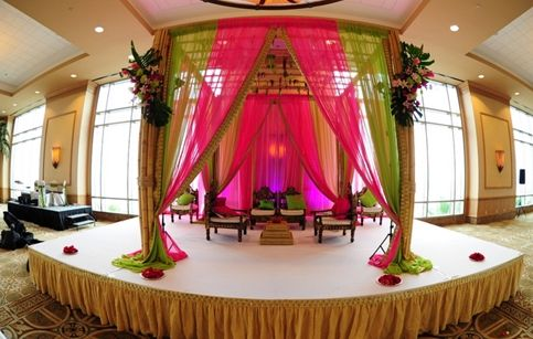 Stage With White Covering Gold Skirting And Pink Green Drape Mandap On Top Via Maharani Weddings