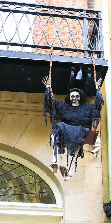 Spooky Halloween neighbor swinging off the balcony on