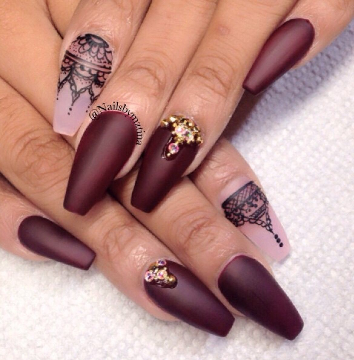 Dark purple plum nails that are coffin shape with gold jewelry ...