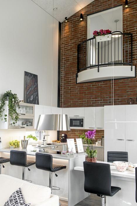 Balcony built to the bedroom to overlook the living space!   Valoisan keittiön värimaailman rikkoo upeasti talon yläkertaan rakennettu ranskalainen parveke. Kukkien ansiosta tunnelma huokuu kesää. Tässä talossa keittiö on virallisesti talon sydän, sillä se hallitsee alakerran avaraa tilaa.