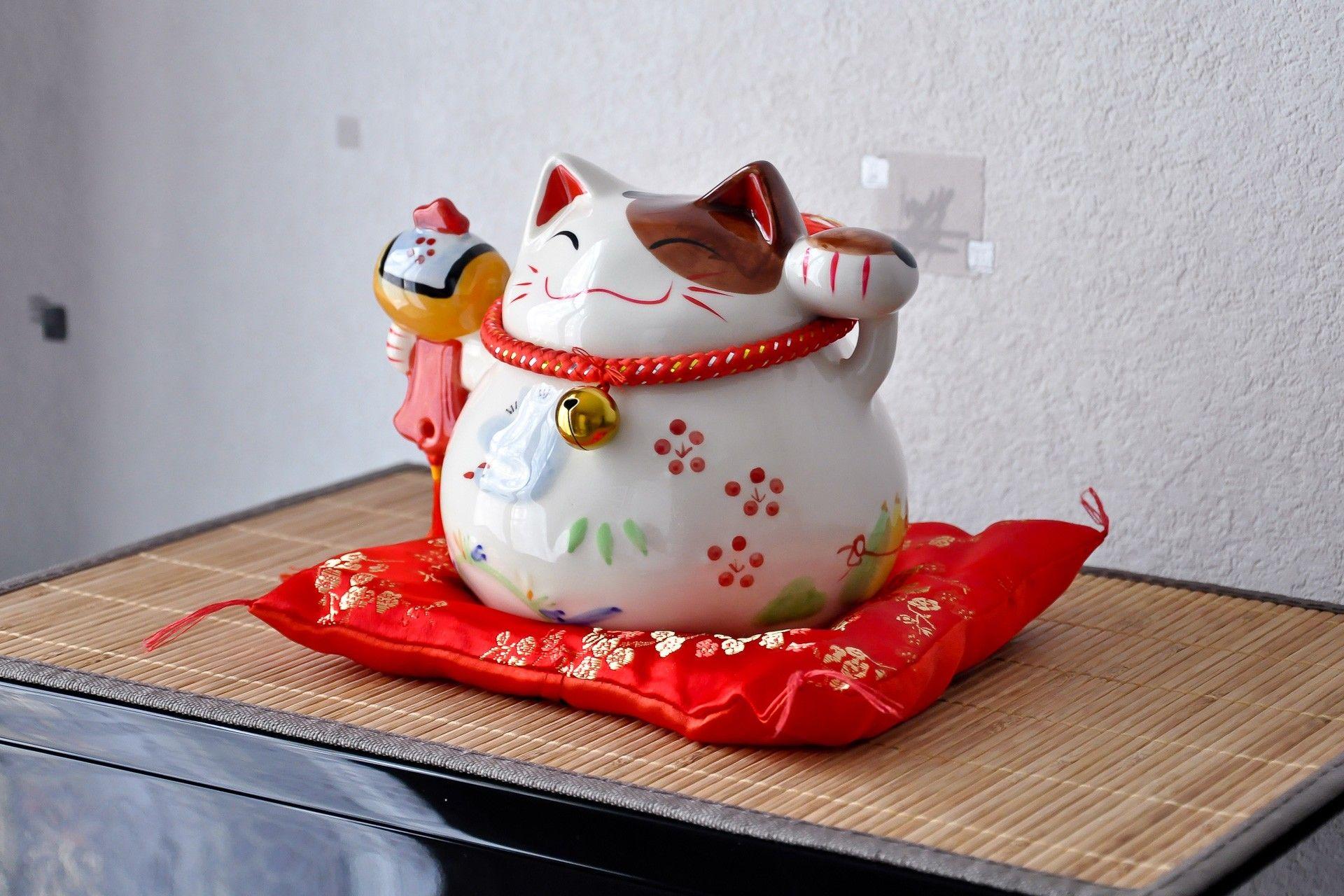 Apportez  un symbole japonais dans votre maison avec cette tirelire Chat Blanc Maneki Neko Nature. Posé sur son coussin rouge, il saura sublimer votre décoration tout en essayant d'attirer la chance et la fortune. Sympathique et originale, cette statuette chat blancheen céramique est un symbole de pureté qui magnifiera votre intérieur.