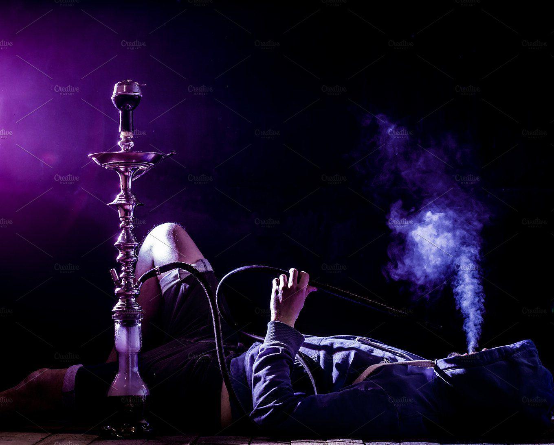 A Man Smokes A Hookah On A Black Background Beautiful Lighting