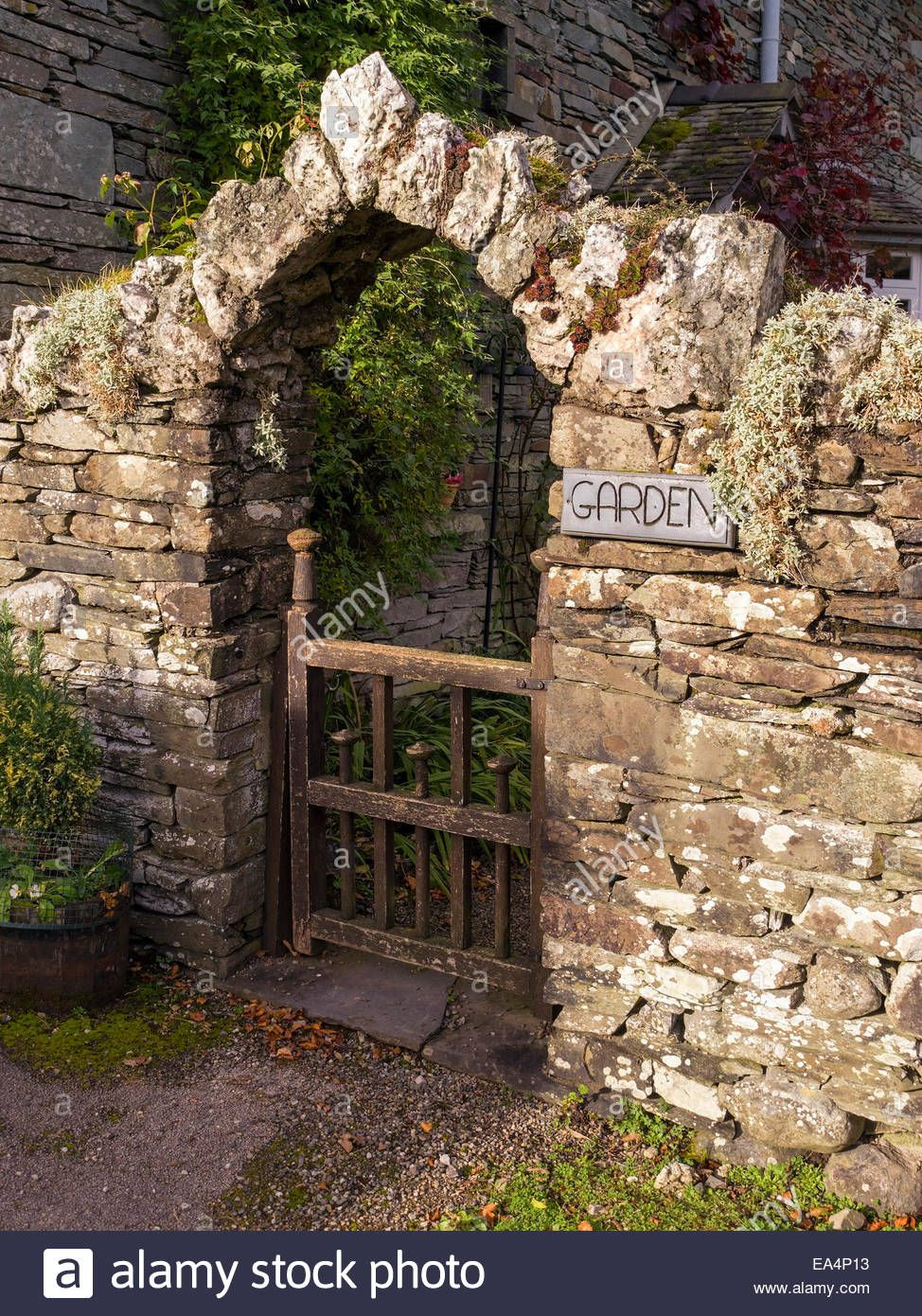 Old Slate Stone Wall With Archway Over Wooden Gate Into Garden