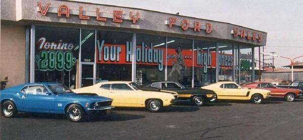 60's Ford dealership with classic Mustangs lined up on the lot ...