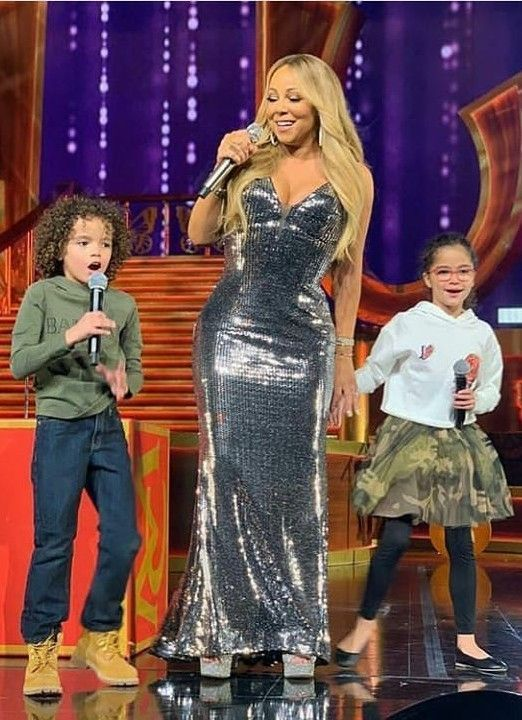 Cutie! Love this photo of Mariah Carey with her twins on stage during her concert. Mariah's son Morocco Cannon looks super stylish wearing this trendy Army Green Balmain Kids Mini Me Sweatshirt. The perfect streetwear look for kids inspired by the Balmain Paris Adult collection. Morocco completed his look with a pair of dark denim jeans and Timberland boots. Twin sister Monroe wore a cool camouflage tulle skirt.  #mariahcarey #demkids #balmain  #celebritykids