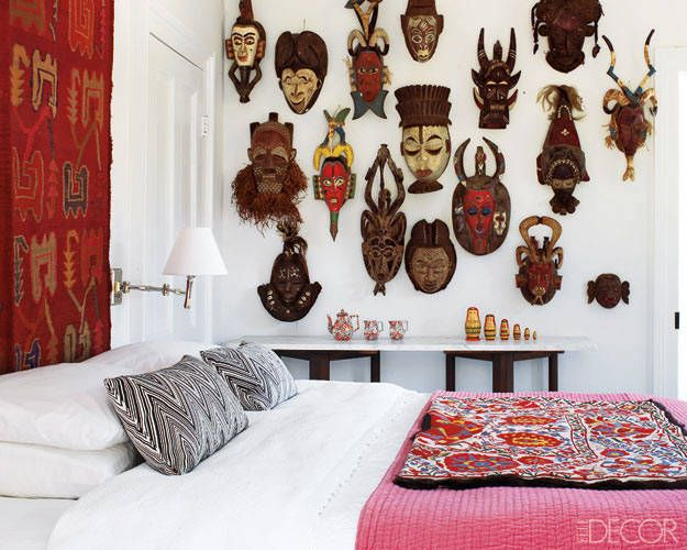 A collection of tribal masks is displayed in a guest room; a tapestry from Argentina hangs above the bed. Tour the entire home   - ELLEDecor.com