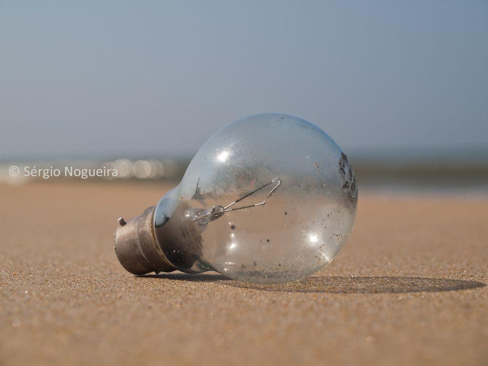 Old light bulb in the beach sand