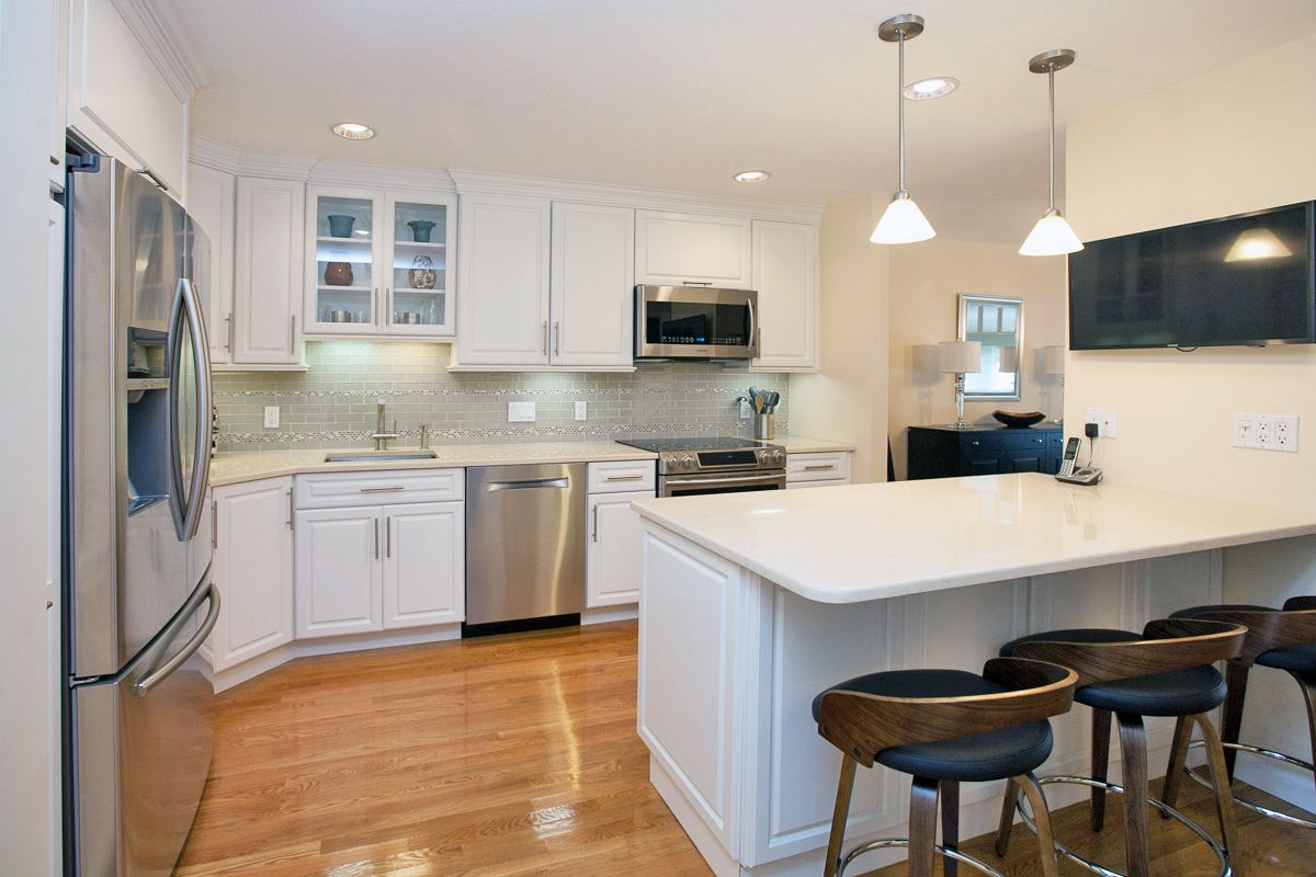 White kitchen cabinets, stainless steel appliances ...