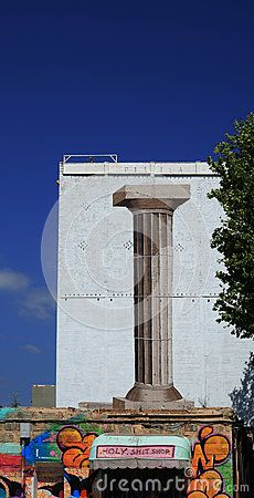 Shot in color, detail on a facade of a building with a giant column painted on, placed in Poblenou, set in Barcelona, Catalonia, Catalunya, España, Spain, Europa, Europe