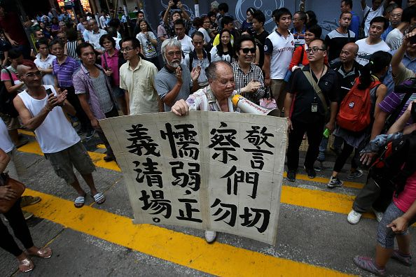 Umbrella Revolution Hong Kong, An anti-protest demonstrator holds a poster in support of the police on a street in Mong Kok on October 22, 2014 in Hong Kong, Hong Kong. Police have begun to take measures to remove the blockades put in place by pro-democracy supporters, as protests entered a fourth week. (Photo by Kong Ng/Getty Images)