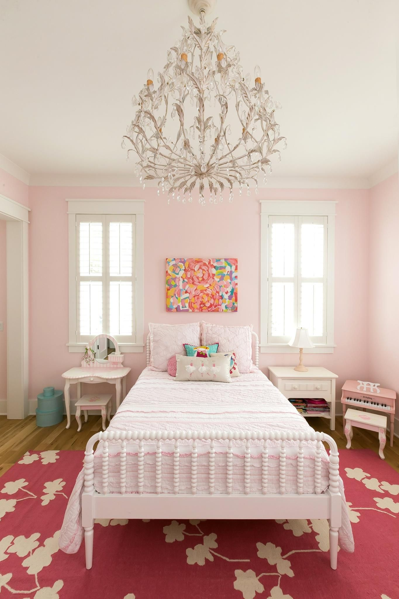 Girls room chandelier white antique bed dark pink rug pale pink walls colorful painting by jennifer latimer white side tables nightstands