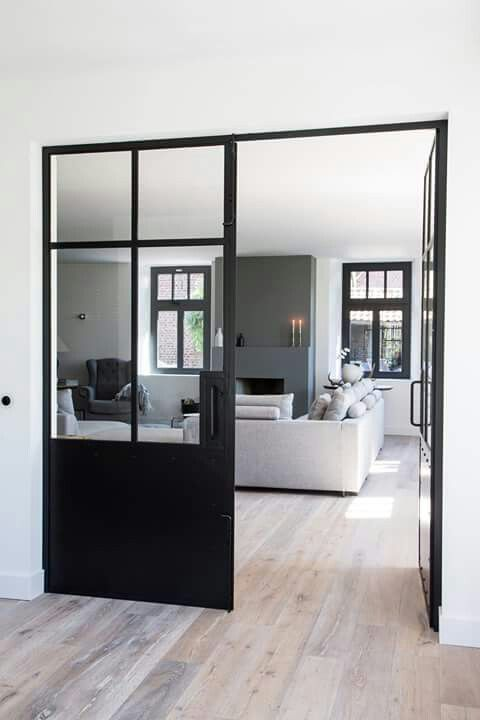 Black steel glazed framework separates the dining area from the kitchen and garden.