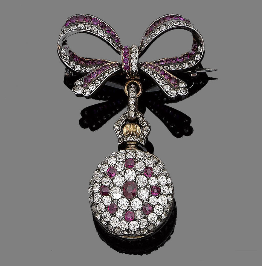 A ruby and diamond fob watch/brooch, circa 1890  The circular-cut ruby, cushion-shaped and old brilliant-cut diamond bow, suspending a detachable similarly-set circular plaque, the reverse revealing a dial with Roman and Arabic numerals, within a rose-cut diamond bezel, cushion-shaped diamonds approx. 2.30cts total, length 5.4cm