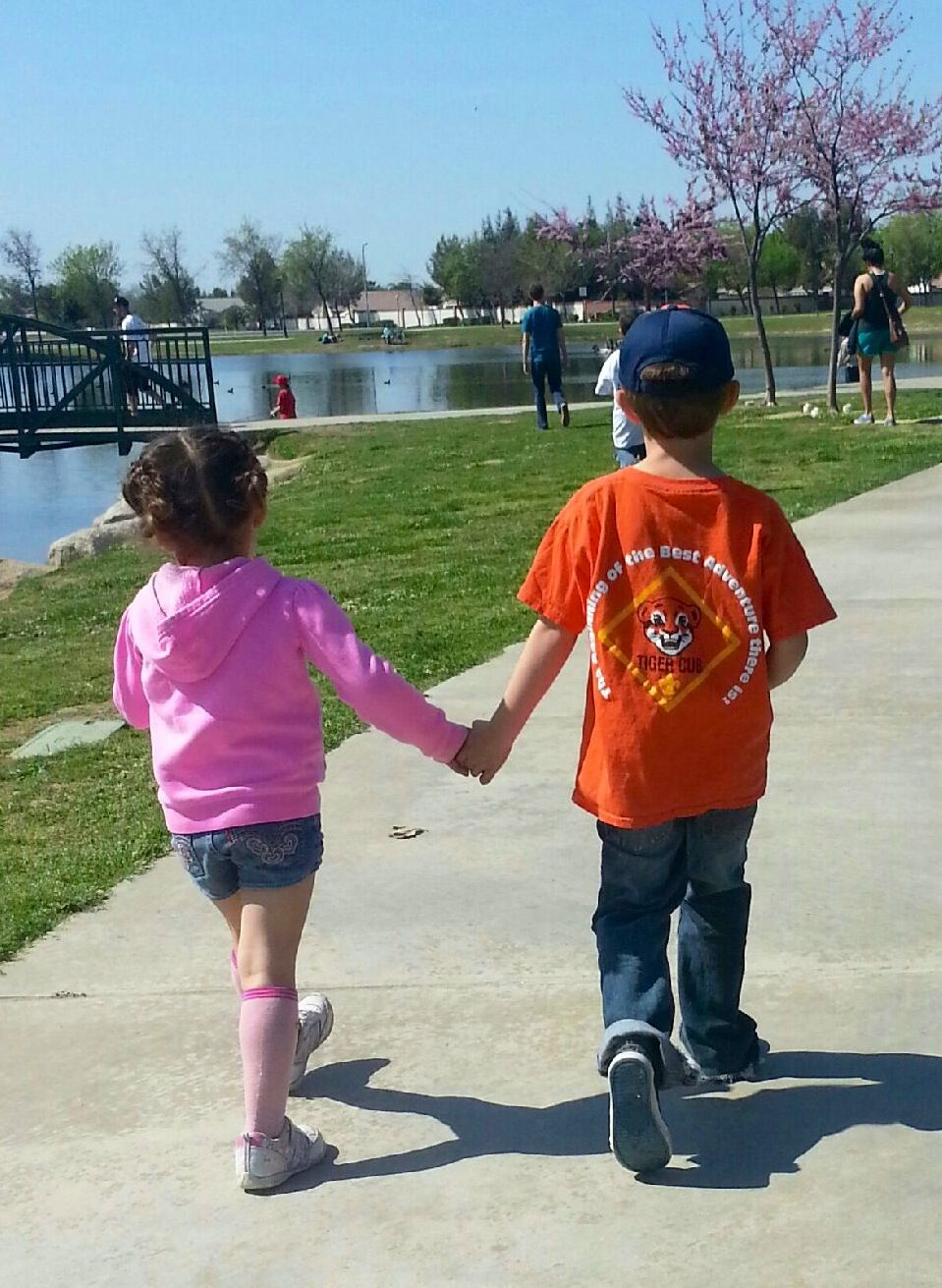 Cub Scout with cystic fibrosis holding hand with friend at CF walk