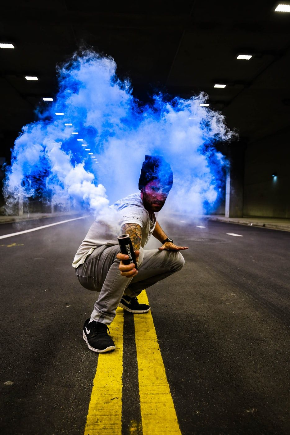 Man Holding Black Tube With Blue Smoke In The Middle Of Road Career In Fashion Designing Fashion Designing Course Fashion Designer List