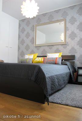 Grey bed with colorful pillows / Harmaa sänky värikkäillä tyynyillä somistettuna