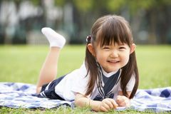 Young Chinese Girl Lying On Blanket In Park
