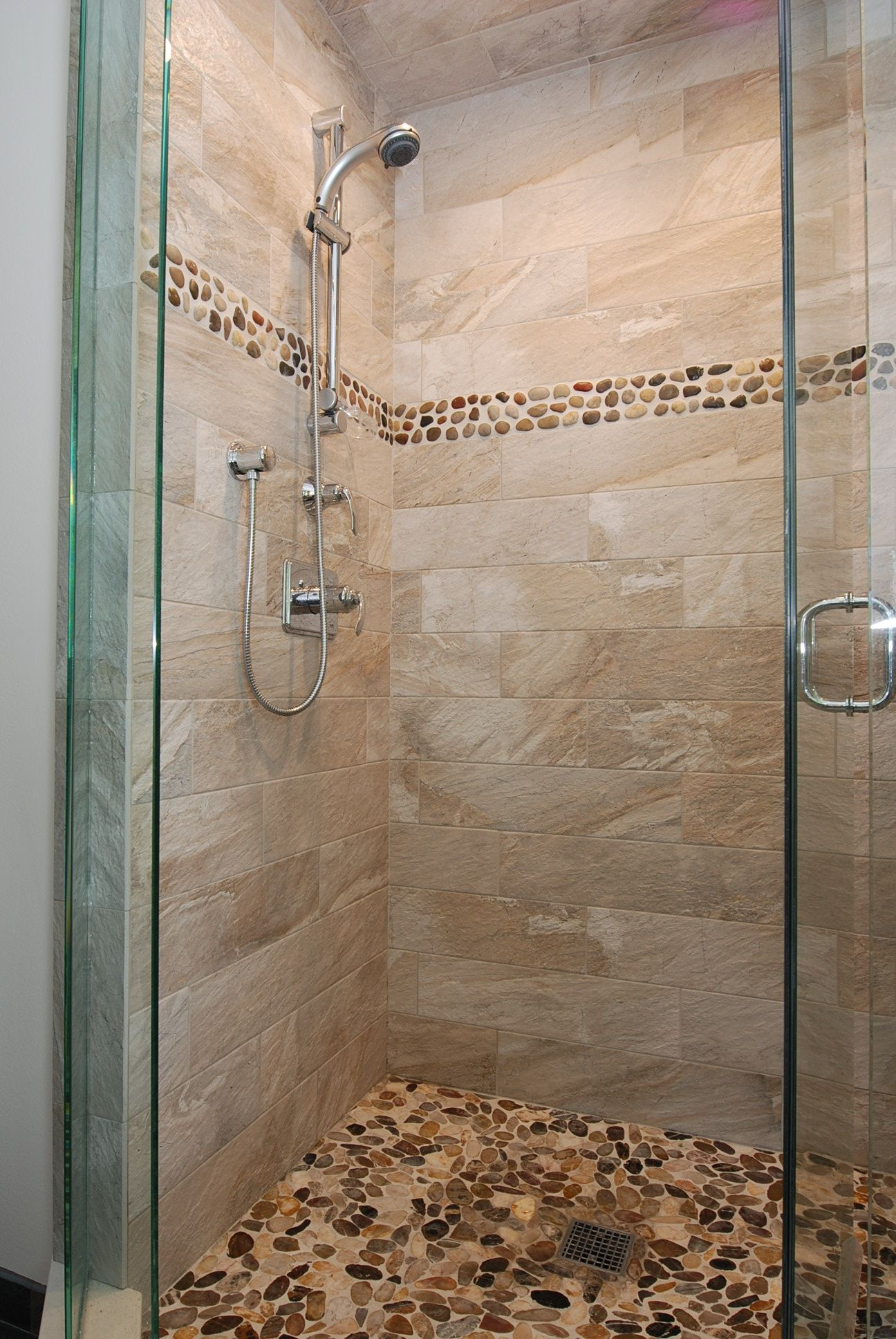 Glass enclosed shower. Gray-brown tile shower with St. Martin Stones ...