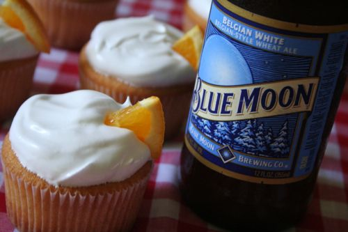 Blue Moon Cupcakes :)  3/4 c unsalted butter, softened  1 3/4 c sugar  2 1/2 c flour  2 1/2 tsp baking powder  1/2 tsp salt  3 eggs, room temperature  1 tsp vanilla  2 drops red food coloring  10 drops yellow food coloring  1/2 tsp orange zest  1 c Blue Moon beer  1/4 c milk  Frothy White Frosting [recipe follows]  small orange slices, for garnish