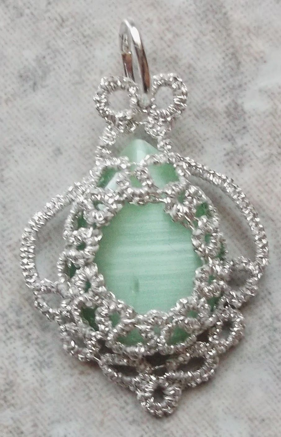 "Silvery Green      A pendent made with two strands of silver sewing thread and green cats-eye.  The pendent is 3/4 X 1 1/4""."