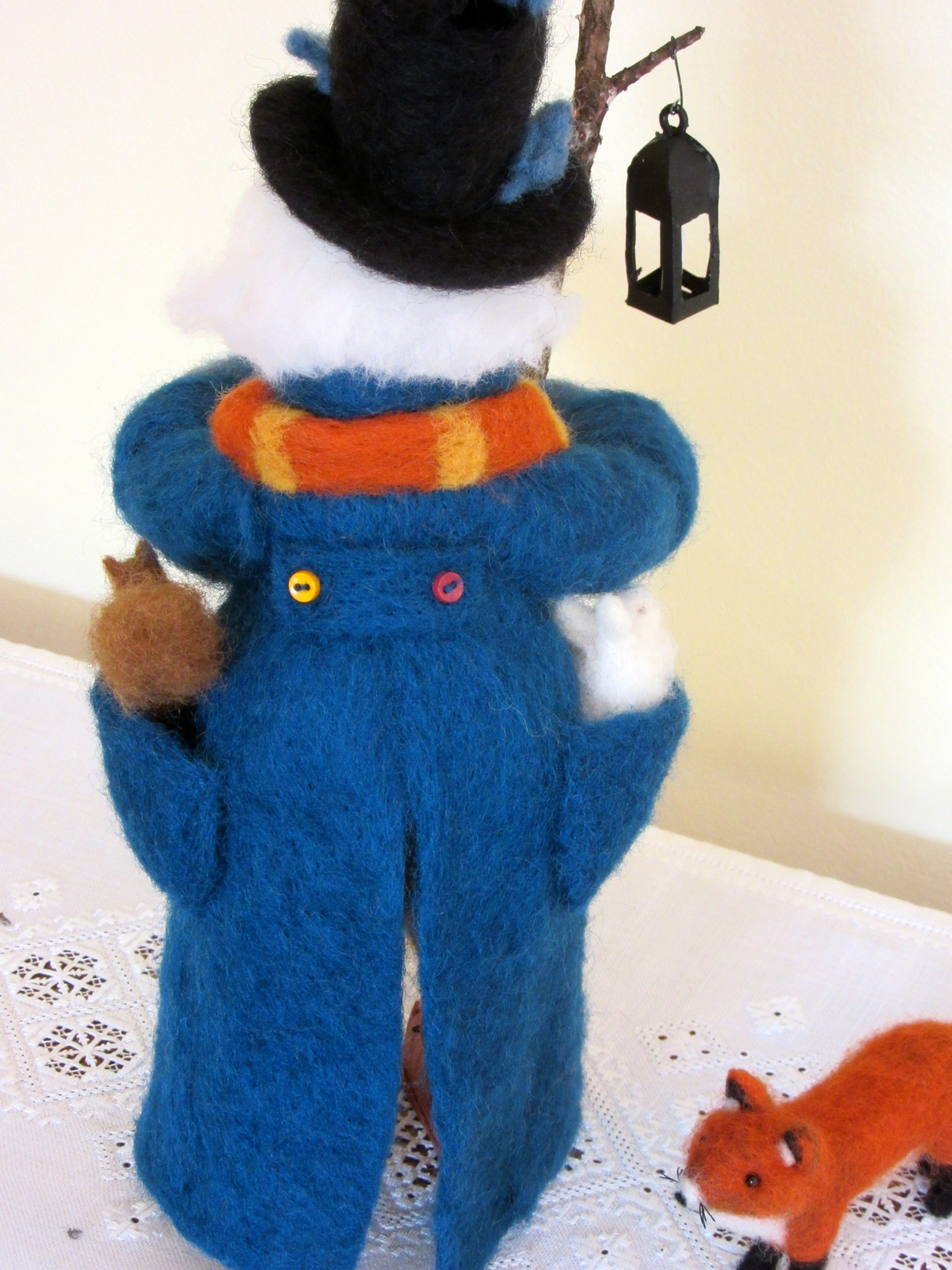 Neeldle felted back view of Father Winter. He has a white rabbit in one pocket and a squirrel in the other.  by Donna Seim