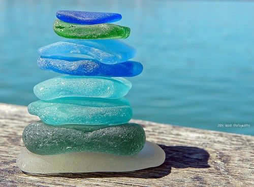 A repin of blue and green sea glass, with water in the background