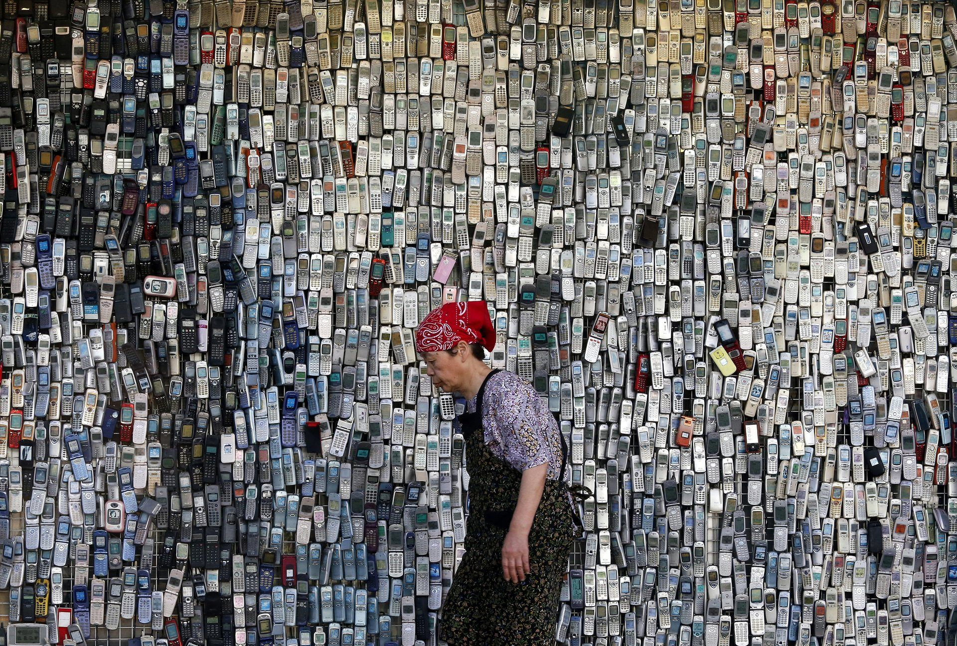 Tokyo, Japan—A woman walks past a wall of mobile phones displayed outside an electronics shop. (Photograph: Shuji Kajiyama/AP) http://www.theguardian.com/news/gallery/2016/jun/02/best-photographs-of-the-day-floods-in-germany-and-a-belgian-panda#img-11