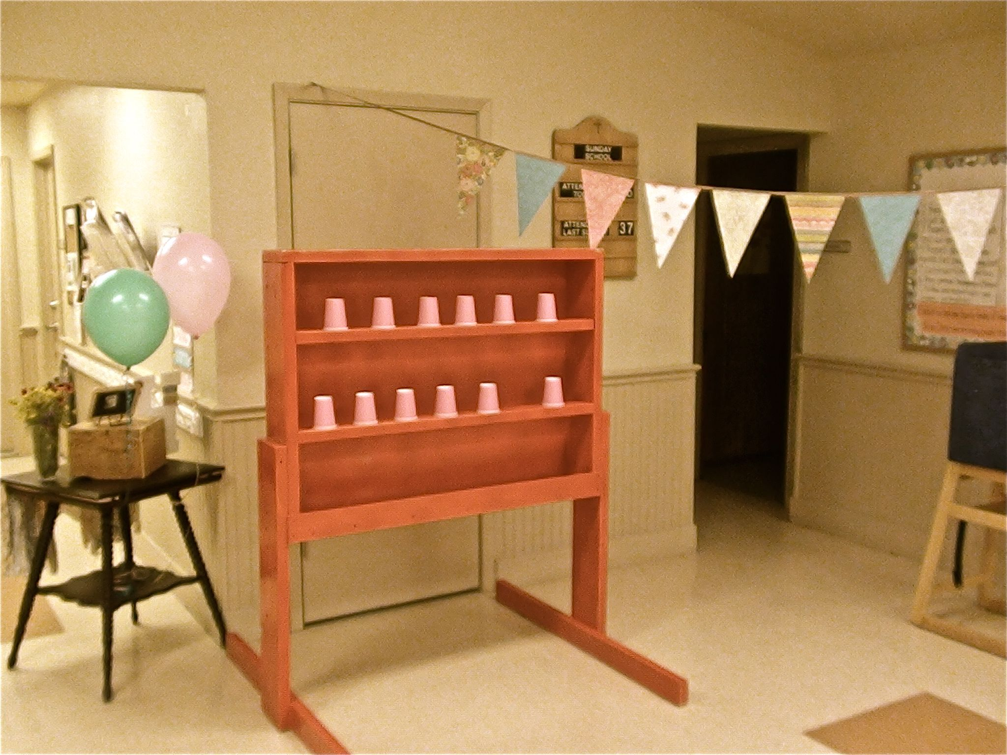 DIY Fair games for a Vintage County fair 1st birthday party. Use nerf guns to shoot cups off the shelf! (I wanted to use tin cans but they were too heavy for the nerf guns to knock off!)