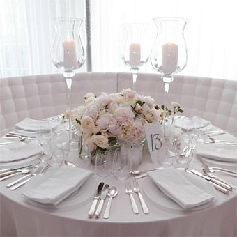 This Centerpiece Incorporates White Botanicals And Frosted Candles To Give It A Fresh