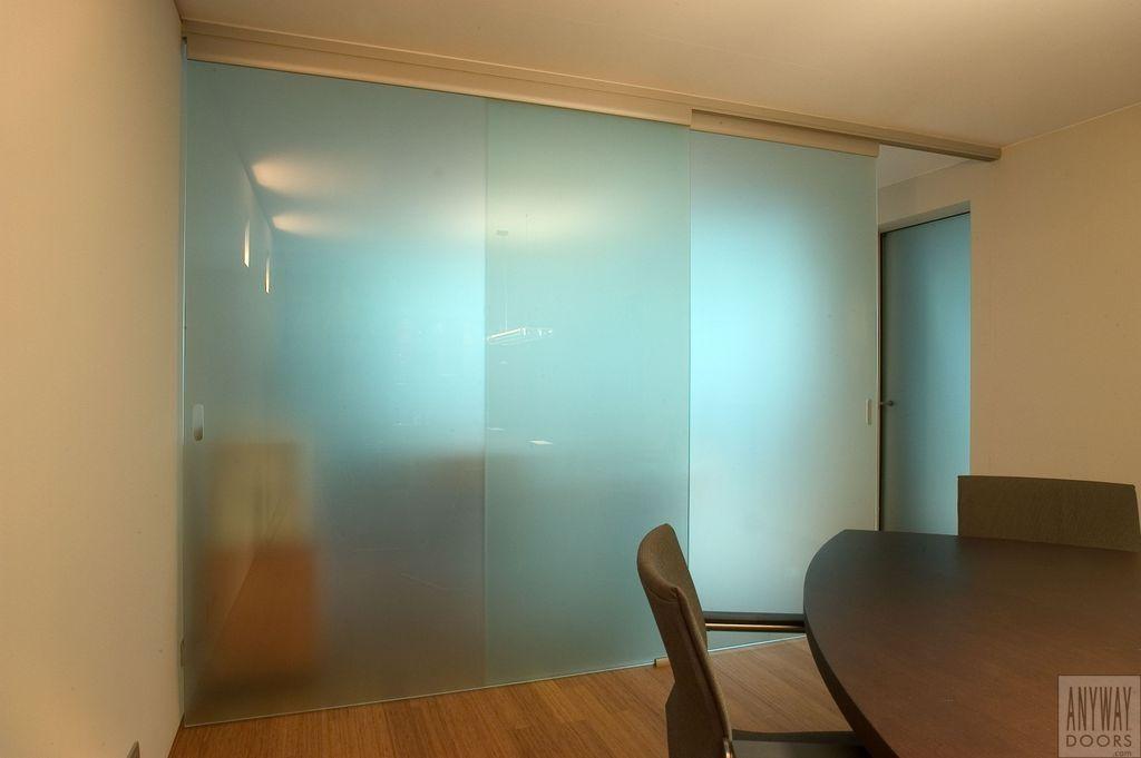 Grote glazen schuifdeuren om bureaus van elkaar te scheiden