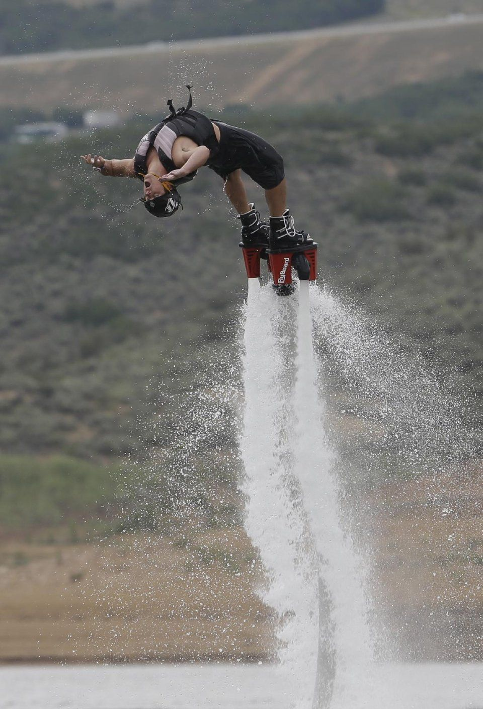 This July 24, 2013, photo, Rocky Mountain Flyboard instructor Chase Shaw flips with his flyboard, on the Jordanelle Reservoir, at Jordanelle State Park, Utah. The Flyboard, which looks like a small snowboard attached to a hose, can propel you 45 feet in the air using water pumped from a personal watercraft like a Jet Ski to the base of the board. New devices that pump water fast enough to make people defy gravity are drawing thrill-seekers eager to try the next new watersport, but Hawaii…