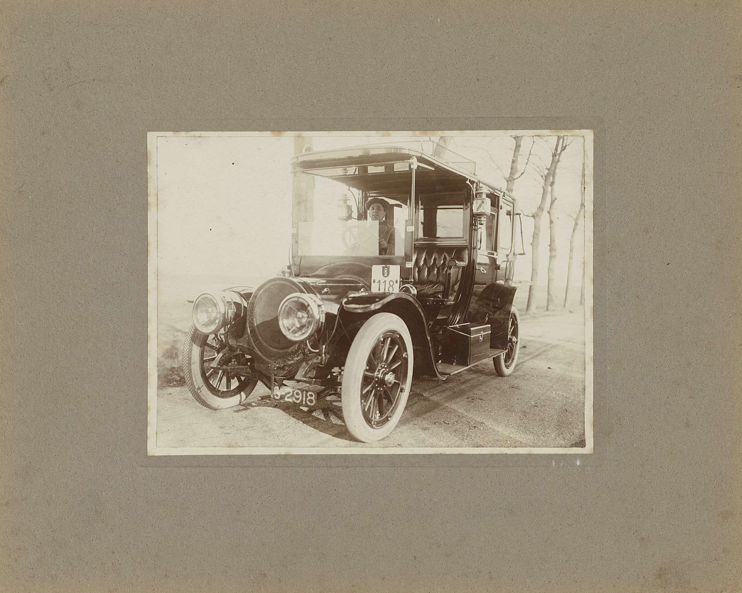 Anonymous | Man in automobiel, nummer 118, voor huis, Anonymous, 1900 - 1920 |