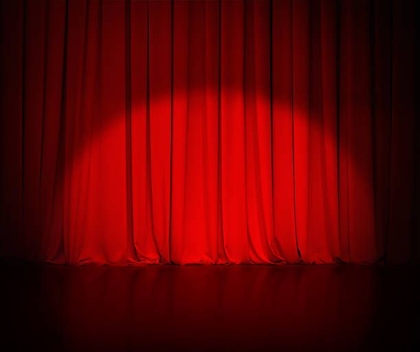 Theatre Red Curtain Or Drapes Background With Light Spot