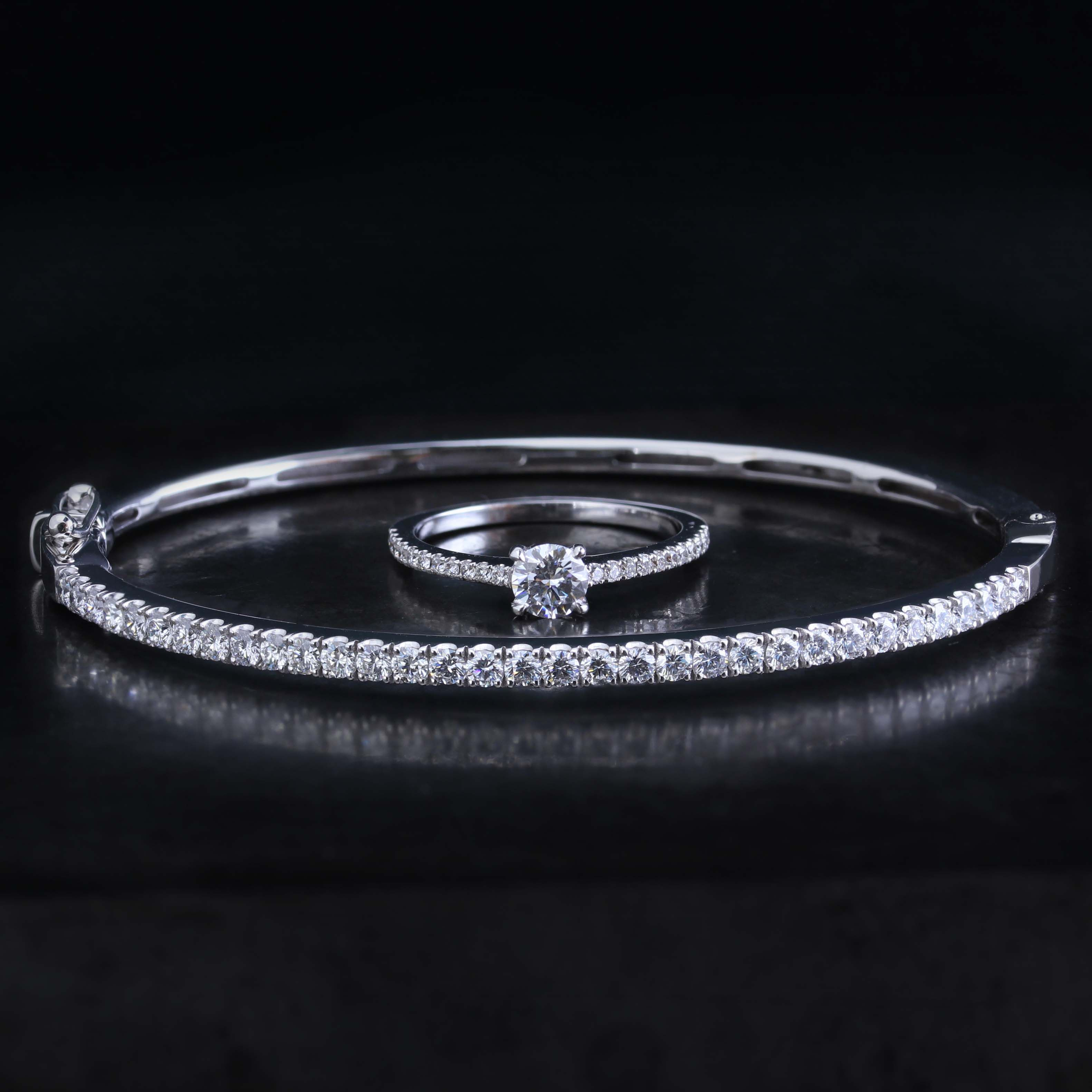 Bangle in white gold with castle set brilliant cut diamonds accompanied by a matching engagement ring.