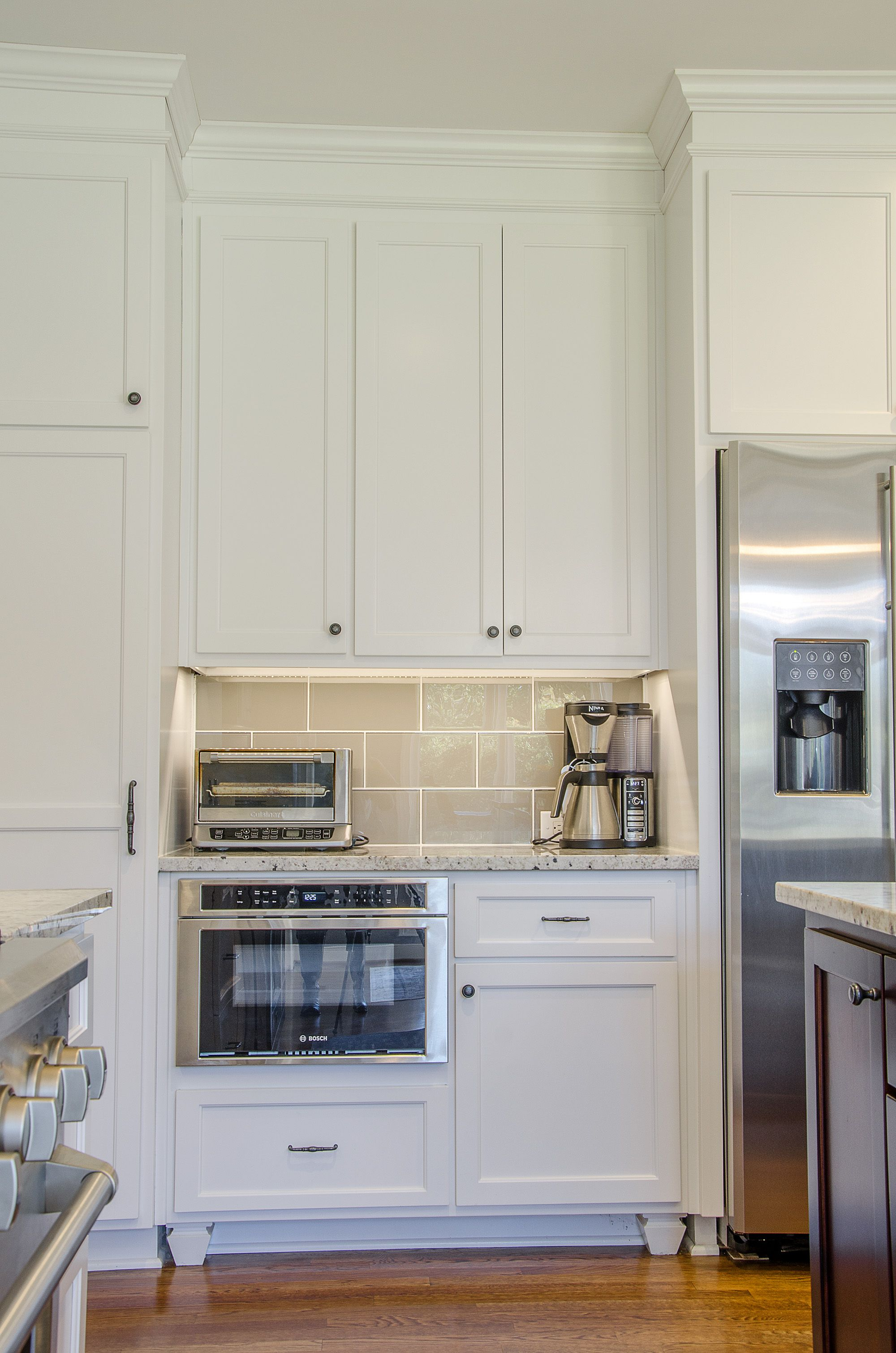 Floor to ceiling custom white kitchen cabinets with stainless steel