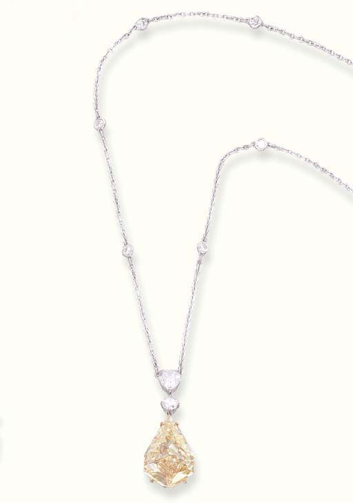 A YELLOW DIAMOND PENDENT NECKLET   Set with a kite-shaped yellow diamond weighing 7.62 carats to the circular-cut and pear-shaped diamond surmount suspended from a fine-link chain with collet-set diamond spacers, 40.5 cm
