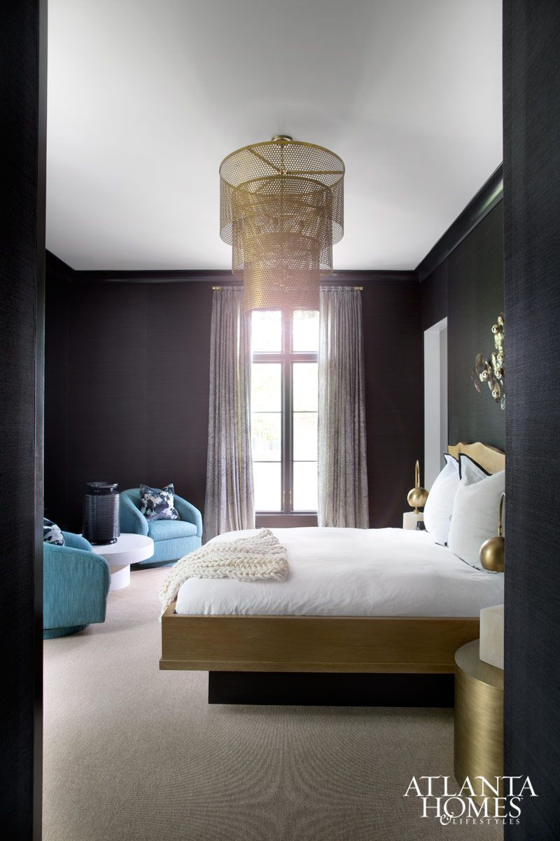 Master bedroom feature wall  This bedroom boasts sleek black grasscloth walls and dramatic brass