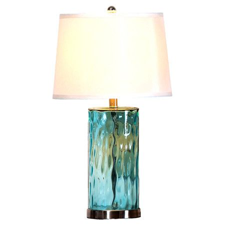 With its cool turquoise hue and textural glass base this intriguing table lamp brings refreshing coastal style to your home decor