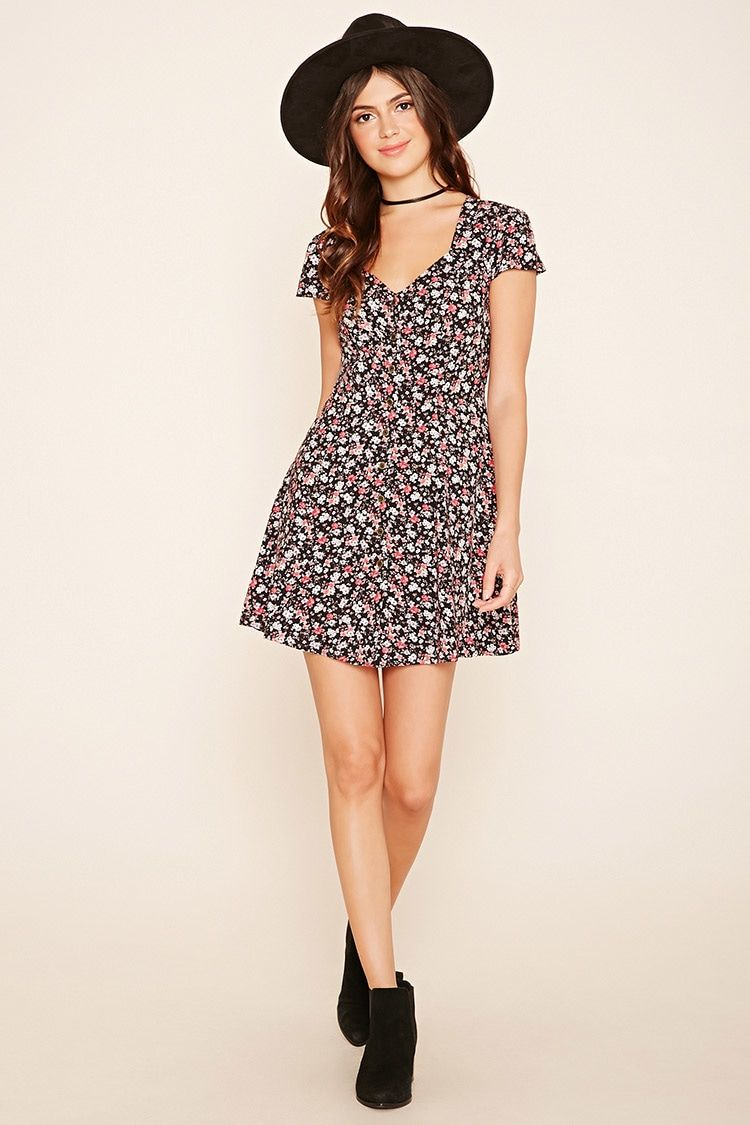 A woven mini dress featuring a floral print, a button-down placket, short sleeves, and an angled V-neckline.