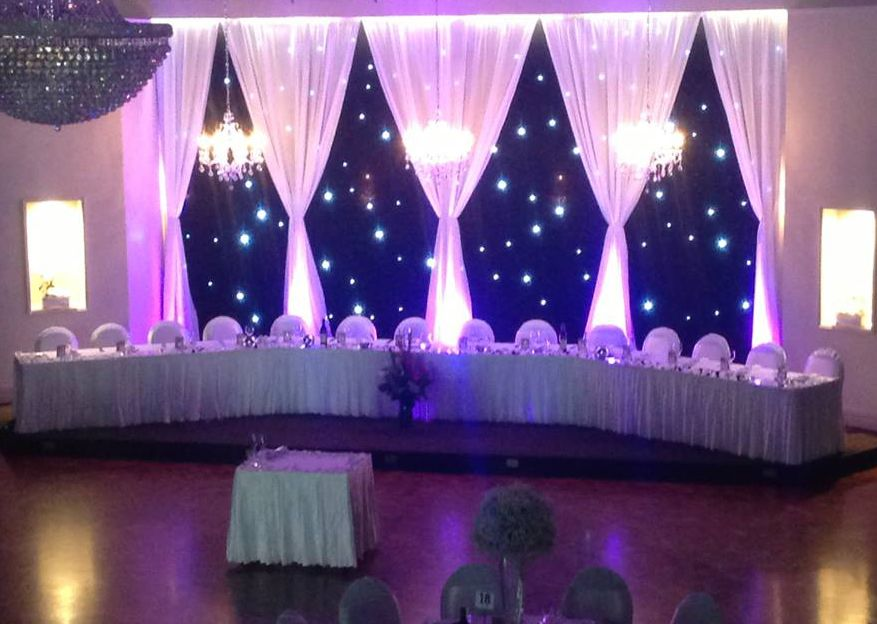Wedding reception backdrop using black drapes, with white gathered drapes,  chandeliers and fairy lights