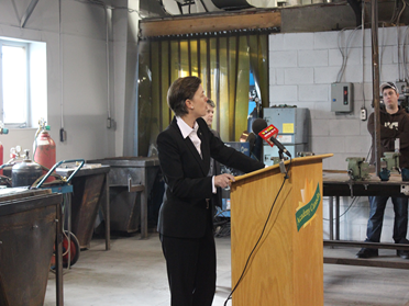 """Dr. Kelli Leitch addresses students, staff, and media about """"Action Plan 2013""""."""