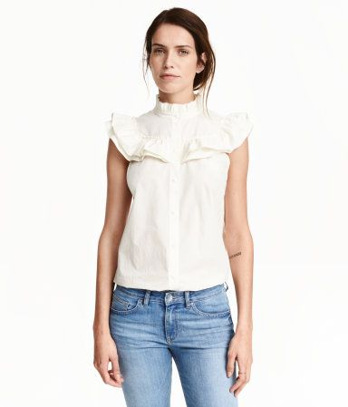 White. Flared blouse in woven cotton fabric with a ruffle-trimmed stand-up collar. Buttons at front, ruffled yoke, and short ruffled sleeves. Pleat at back