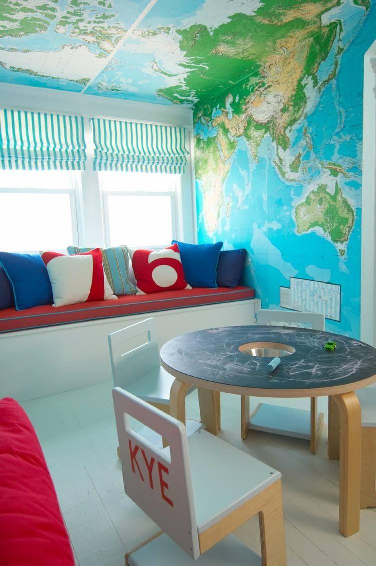 salle de jeux enfant amnage avec une banquette dcore de coussins un papier peint carte du monde une table ronde plateau tableau noir
