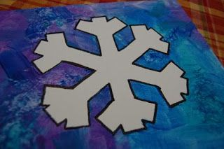 Put masking tape in the shape of a snow flake, let your child blow paint, or sponge paint over the entire page.  Wait for it to dry, then peel off the tape.
